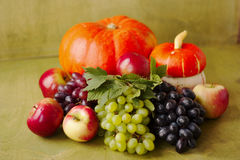 One pumpkin, apples, grapes on a green wooden background Royalty Free Stock Photography