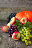 One pumpkin, apples, grapes on a wooden background Royalty Free Stock Photo