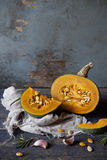 One pumpkin cut in half on rustic blue wooden table with rosemary sprigs and garlic Royalty Free Stock Image