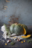 One pumpkin cut in half on rustic wooden table and scraped background with rosemary and garlic Royalty Free Stock Photo