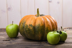 One pumpkin and three apples royalty free stock images