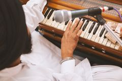 Punjabi Singer with black turban is playing harmonium and singing at Gurudwara. One Punjabi Singer with black turban is playing harmonium and singing at royalty free stock image