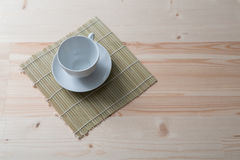 One pure white ceramic Cup and saucer stands on a wooden table.  Stock Photos