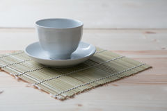 One pure white ceramic Cup and saucer stands on a wooden table.  Stock Images