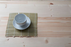 One pure white ceramic Cup and saucer stands on a wooden table.  Stock Photography