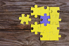One purple puzzle and many yellow puzzles Royalty Free Stock Images