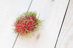One Rambutan on wooden panels Royalty Free Stock Images