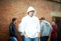 One of rappers. Portrait of angry guy looking at camera with his friends on background Stock Photography