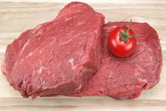 One Raw Beef Steak And Tomato Close-Up. Single Raw Beef Steak And Tomato Close-Up On Wood Background Stock Photo