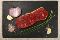 Raw beef steak meat cut and spices on black board Royalty Free Stock Images