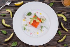 One raw piece of salmon fillet on white plate. Flat lay, fish and avocado and vegetables on wooden table. One raw piece of salmon fillet on white plate. Flat Royalty Free Stock Images