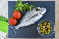 One ready to cook raw bream fish with vegetables on stone slate. Board. Top view Royalty Free Stock Photo