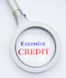 One reason for the recession. A large magnifier focusing on the words excessive credit referring to sub prime loans and bloated lending by banks. A simple stock image