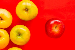 One red apple standing out from a group of other apple on a red Stock Photos