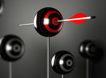 Surpassing Oneself or Self-Transcendence Concept. One red arrow hitting the center of a ball target with other blur targets around, black background with light Royalty Free Stock Image