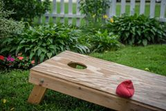 One red bag on hommade wood corn hole game board. Single red bean bag laying on plywood cornhole game board in backyard royalty free stock image