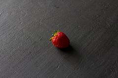 One red beautiful strawberry close-up, on a black dark concrete background. Minimalism. Side view, Copy Space For Your Text. Macro. One red beautiful strawberry stock images