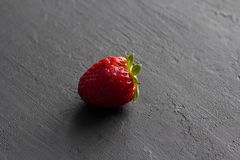 One red beautiful strawberry close-up, on a black dark concrete background. Minimalism. Side view, Copy Space For Your Text. Macro. Shooting royalty free stock photography