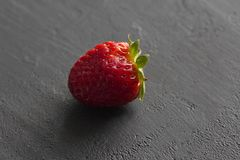 One red beautiful strawberry close-up, on a black dark concrete background. Minimalism. Side view, Copy Space For Your Text. Macro. Shooting royalty free stock images
