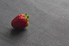 One red beautiful strawberry close-up, on a black dark concrete background. Minimalism. Side view, Copy Space For Your Text. Macro. Shooting royalty free stock image