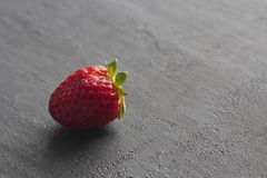 One red beautiful strawberry close-up, on a black dark concrete background. Minimalism. Side view, Copy Space For Your Text. Macro. Shooting stock image