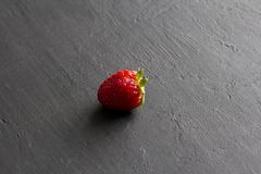 One red beautiful strawberry close-up, on a black dark concrete background. Minimalism. Side view, Copy Space For Your Text. Macro. One red beautiful strawberry royalty free stock photography