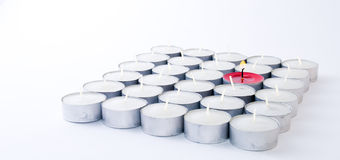 One red candle among lots of white candles Royalty Free Stock Images