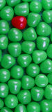 One red candy. A full frame image of a single red candy and a cluster of green candy royalty free stock images