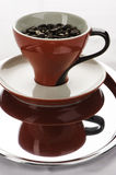 One red coffe cups with beans. One coffe cups with beans one red and other white on the metal tray Royalty Free Stock Images