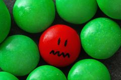 One red drop with painted sad face. Among green ones. Difference and uniqueness concept royalty free stock images