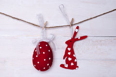 One Red Easter Bunny And Easter Egg Hanging On Line. A Red Easter Bunny With Hearts And A Big Easter Egg Which Is Dotted And With A Loop And Ribbon Hanging On A Stock Photography
