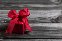 One red festive christmas present on wooden shabby background.
