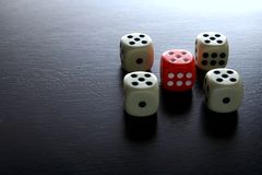 One Red game dice and four white game dice Stock Photo