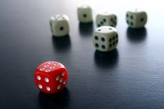 One Red game dice in front of five white game dice Royalty Free Stock Photography