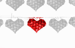 One red heart lamp hanging on wire with many grey heart lamp. On white background, Love concept,leave space for adding text Royalty Free Stock Image