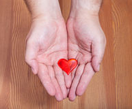 One red heart in male hands. With wooden background Stock Image