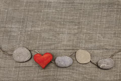 One red heart with stones on wooden background.