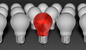 One red light bulb among grey ones on grey textured background Stock Photography