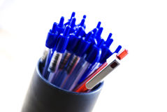 One red and many blue pens. One pen and many blue pens in a can. The focus is on the red pen. Taken with a macro lens Stock Photography