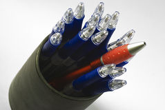 One red and many blue pens. One pen and many blue pens in a can. The focus is on the red pen. Taken with a macro lens Royalty Free Stock Image