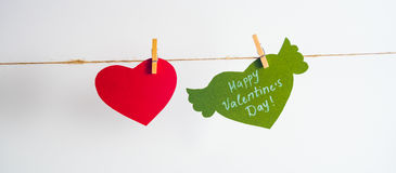 One red paper heart and one green heart with congratulation and wings fixed with clothespins on a cord. White background.  Royalty Free Stock Photo