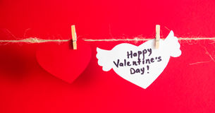 One red paper heart and one white heart with congratulation and wings fixed with clothespins on a cord. Red background. Royalty Free Stock Image