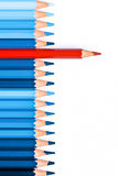 One red pencil among blue ones isolated on white background Stock Photography