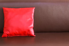One red pillow on the brown leather sofa Royalty Free Stock Photography