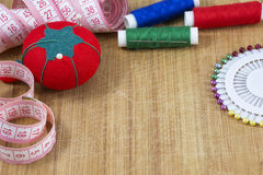 One red pincushion, tape and colourful threads with needle Royalty Free Stock Photos