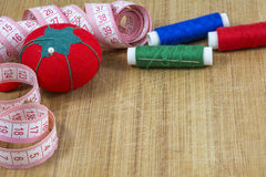 One red pincushion, tape and several threads with needle Royalty Free Stock Image