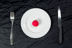 One red radish on white plate on black background with fork and knife. Stock Photos