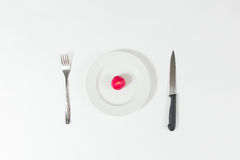 One red radish on white plate on white background with fork and knife. Stock Photography