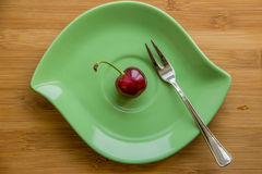 One red ripe cherries on a green plate Royalty Free Stock Images
