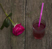One red rose and glass of juice, on an old table Royalty Free Stock Images